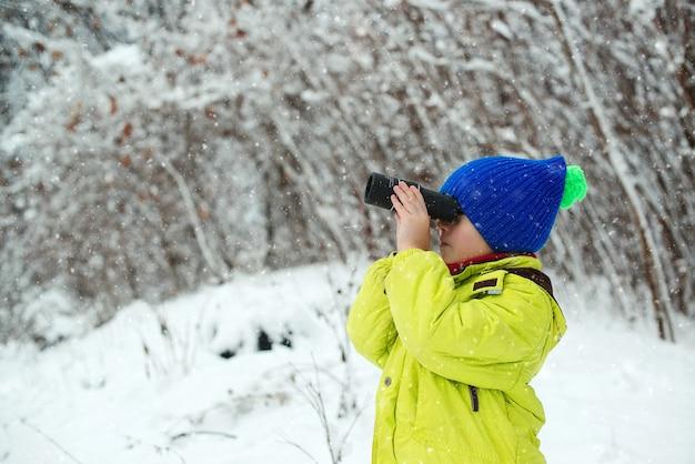 冬の森を歩いて幸せな子。雪に覆われた森のかわいい子供探検家。単眼を探している子供。家族の冬休み。自然の中で冬の楽しみ。家族での休暇、雪の日、そして幸せな子供時代。