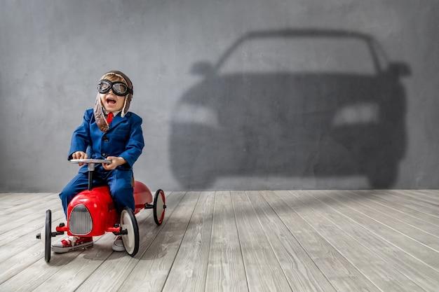 Счастливый ребенок хочет участвовать в гонках. забавный ребенок мечтает о машине.