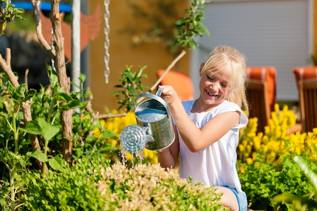 Happy child watering flowers
