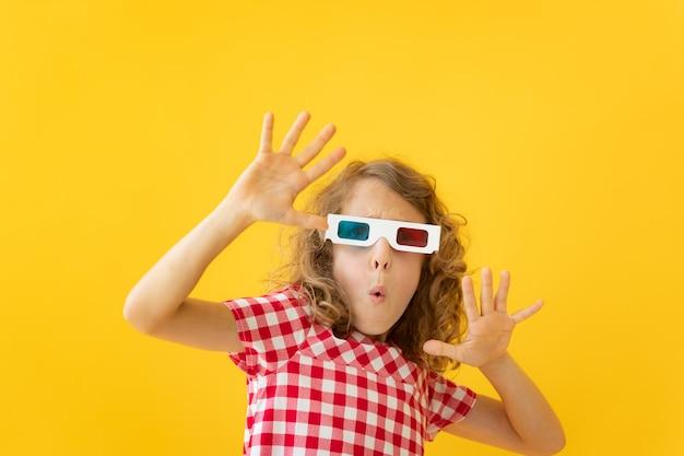 Счастливый ребенок в очках 3d. удивленная девушка против желтой стены. концепция времени кино и кино