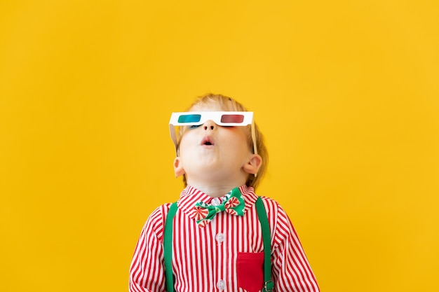 Счастливый ребенок в очках 3d. удивленный ребенок против желтой стены. концепция времени кино и кино
