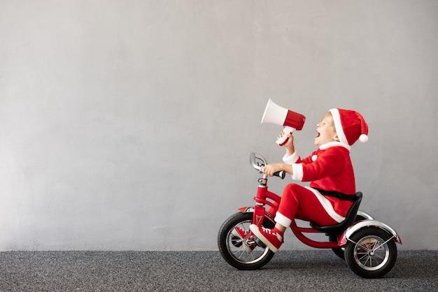 크리스마스 의상을 입고 행복한 아이 자전거를 타는 아이