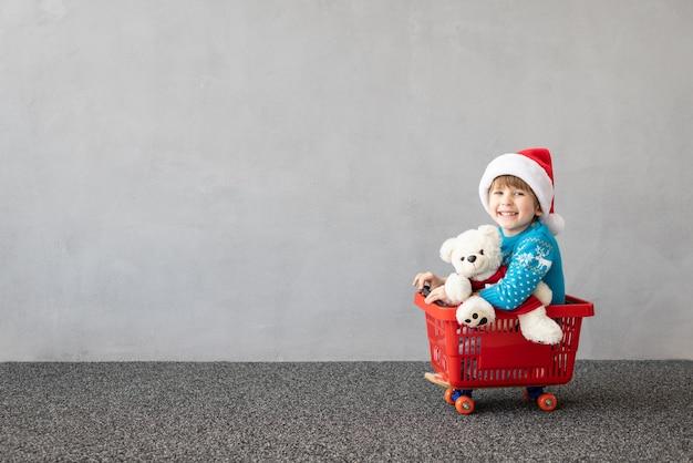 크리스마스 의상을 입고 행복한 아이 쇼핑 카트를 타는 아이