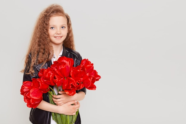 Happy child wearing leather jacket embracing big bouquet of tulips, looking at front with smile