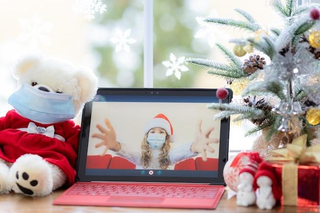 医療マスクを身に着けている幸せな子ビデオチャットで女の子の挨拶