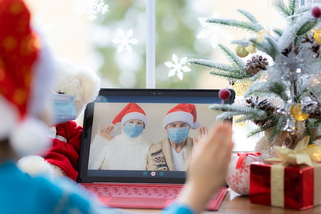 Happy child wearing medical mask grandpa and grandma greeting in video chat