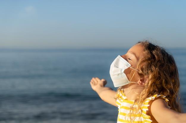 青い空を背景に屋外で医療マスクを身に着けている幸せな子