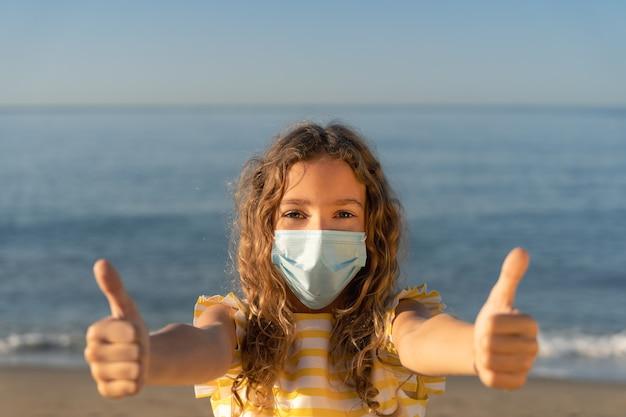 青い空を背景に屋外で医療マスクを身に着けている幸せな子。