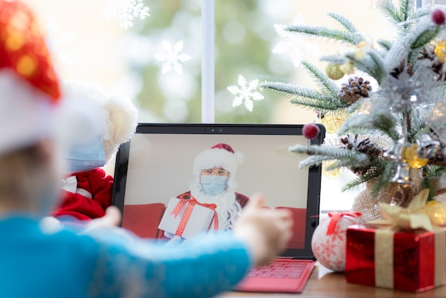 Happy child wearing medical mask santa claus greeting in video chat