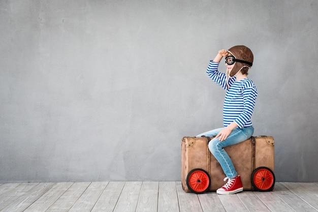 파일럿 모자와 안경을 쓴 행복한 아이는 복사 공간이 있는 회색 벽 배경에서 놀고 있습니다.