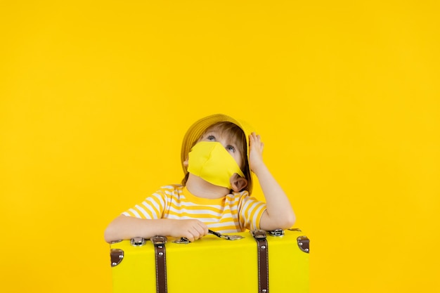休暇を夢見て保護マスクを身に着けている幸せな子供。コロナウイルスcovid-19パンデミック時の夏休み。