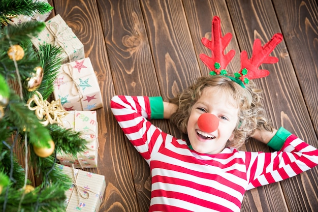 Happy child wearing reindeer rudolph. funny kid on christmas eve. xmas holiday concept