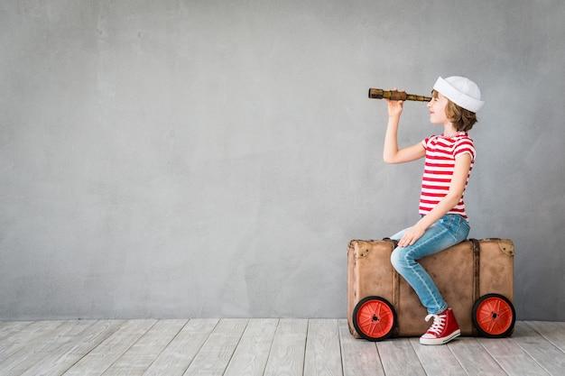 Счастливый ребенок в матроске играет в помещении с подзорной трубкой на сером фоне с копией пространства