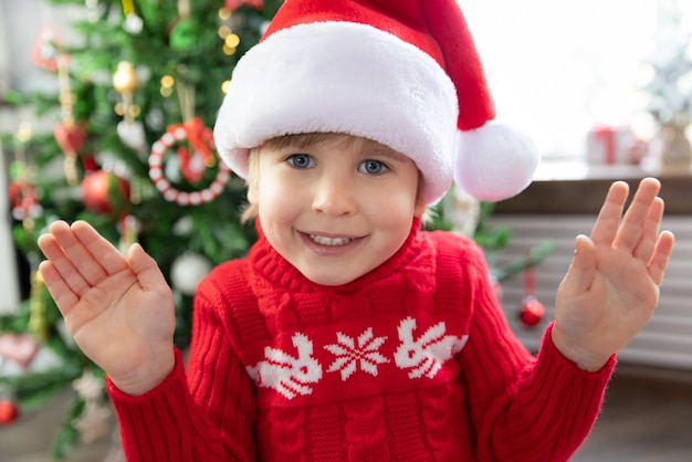 Happy child wearing santa claus hat kid playing at home