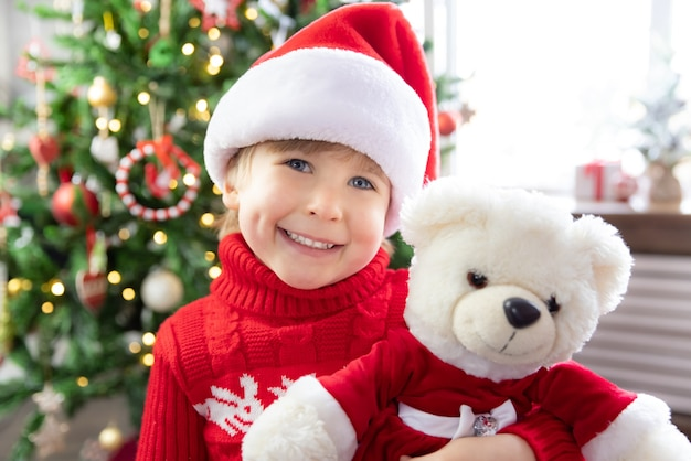 Happy child wearing santa claus hat kid playing with teddy bear at home