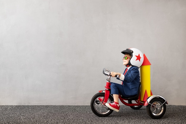 Happy child wearing suit riding bicycle against grey concrete wall. childhood dreams and business idea concept