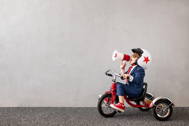 회색 콘크리트 벽 표면에 양복을 타고 자전거를 입고 행복 한 아이
