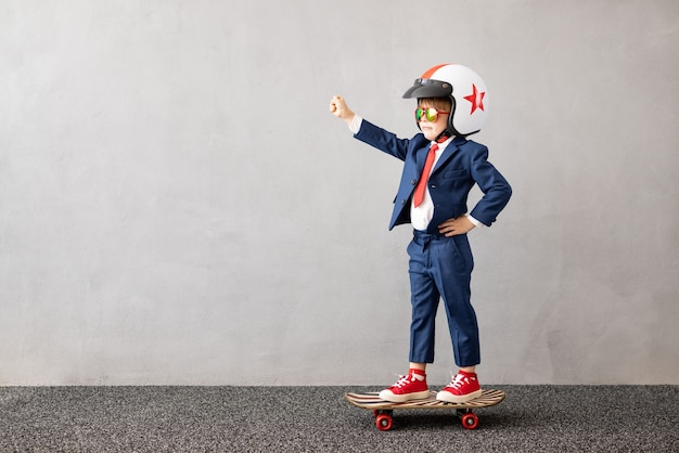 Happy child wearing suit riding skateboard against grey concrete wall. childhood dreams and business idea concept