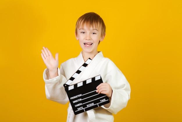 Happy child in white kimono making video or movie.