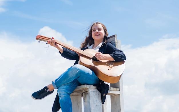 空の背景、音楽のアコースティックギターと幸せな子。