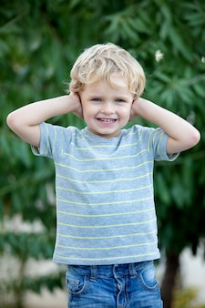 Happy child with blue t-shirt in the garden
