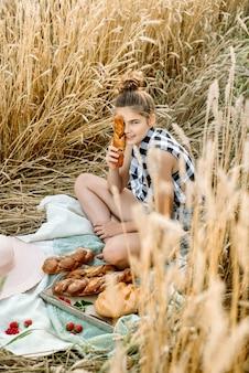 黄色い秋の麦畑でパンと幸せな子。成熟した耳のある畑。女の子は寝具、新鮮な果物とベリー、パンとロールパンにバスケットに座っています。アウトドアビレッジピクニック。
