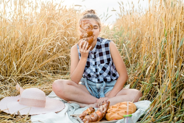 Happy child with bread in yellow autumn wheat field. a field with mature ears. a girl sits on a bedspread, fresh fruits and berries, bread and rolls in a basket. outdoors village picnic.