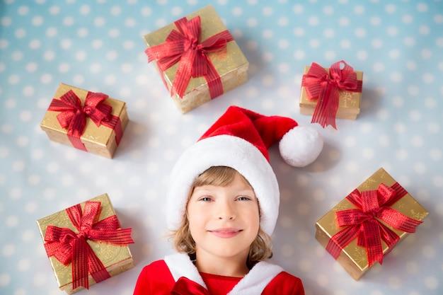 Счастливый ребенок с коробками подарка рождества. рождественский праздник концепции. вид сверху