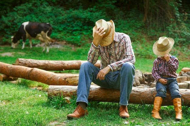 フィールドで自然の中でカウボーイの親と幸せな子