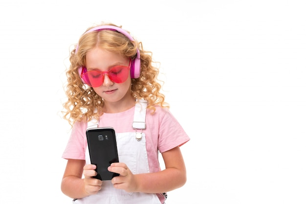 Happy child with fair red curly hair chatting with friends and listen to music