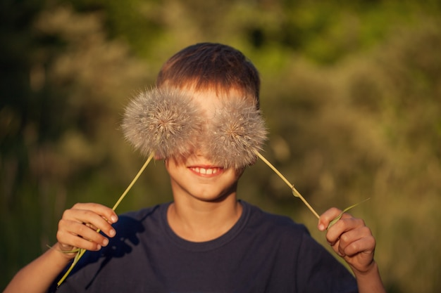 Happy child with fluffy dandelion eyes in a summer day. boy is smiling, lifestyle