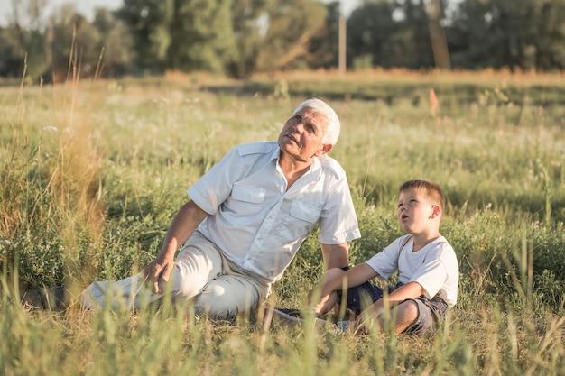 Счастливый ребенок с дедушкой, играя на лугу