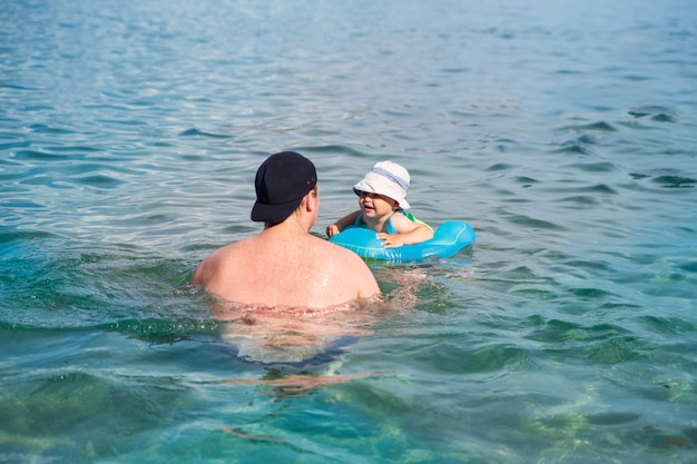 A happy child with his father swims in a swimming ring in the sea