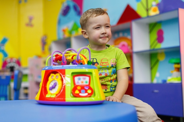 Happy child with  interesting toy in preschool and kindergarten boy is playing with a colorful toy