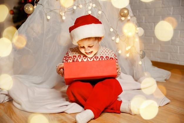 クリスマスツリーの近くに魔法の贈り物を持つ幸せな子供新年あけましておめでとうございます