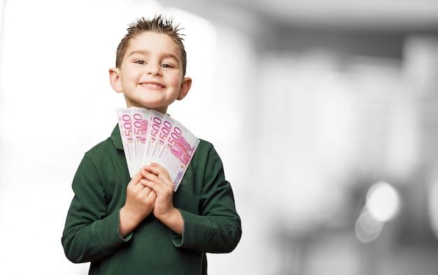 Счастливый ребенок с большим количеством законопроектов в руке