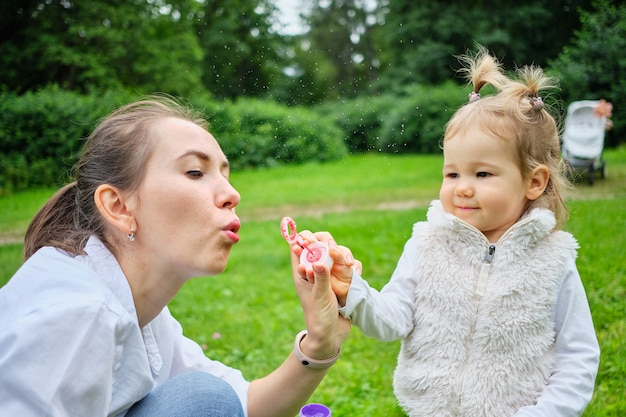 Счастливый ребенок с мамой дует мыльные пузыри.