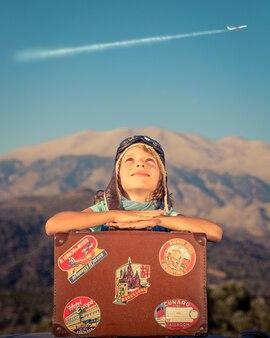 백그라운드에서 비행하는 비행기와 산에 대 한 오래 된 가방과 함께 행복 한 아이