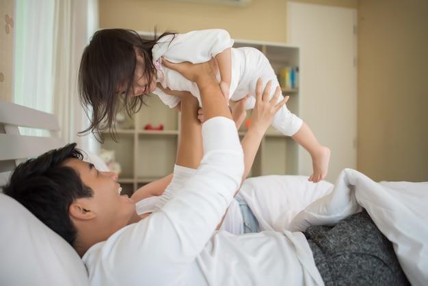 家庭のベッドで遊んでいる両親と幸せな子供
