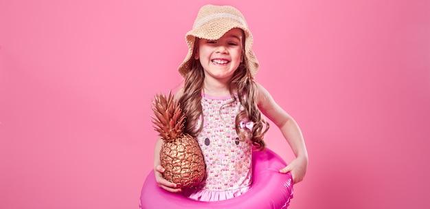 Счастливый ребенок с ананасами на цветном фоне