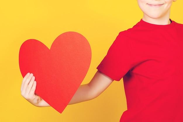 黄色の背景に赤いハートの幸せな子。休日の概念。赤い紙の心を持ってかわいい笑顔の少年。