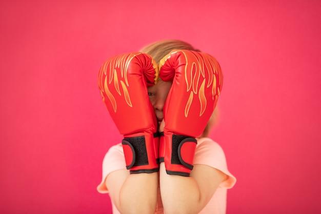 Счастливый ребенок с красными боксерскими перчатками в форме сердца на розовом фоне концепция дня святого валентина