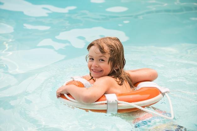 浮き輪と幸せな子。プールでの夏のパーティー。スイミングプールの子供。アクアパークで楽しんでいる少年。