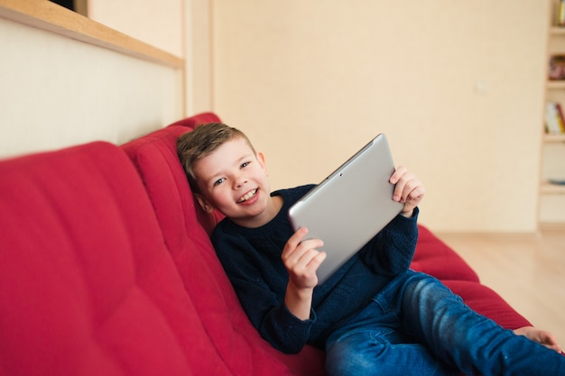 Happy child with tablet at home