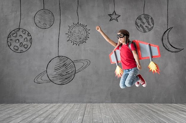 Счастливый ребенок с игрушечными бумажными крыльями, играя дома.