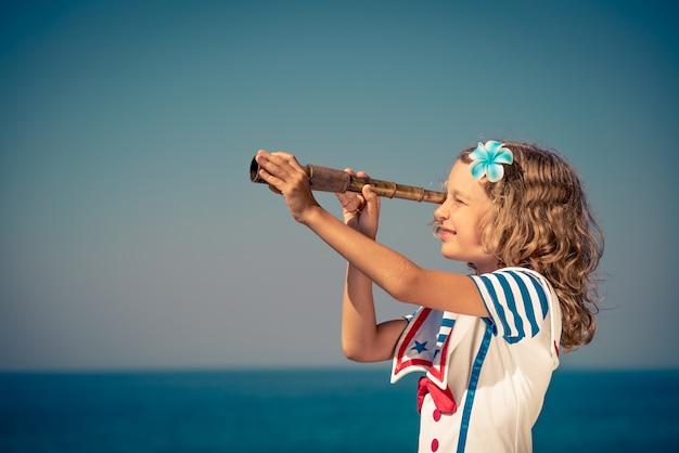 Счастливый ребенок со старинной подзорной трубой ребенок веселится на летних каникулах концепция путешествий и приключений
