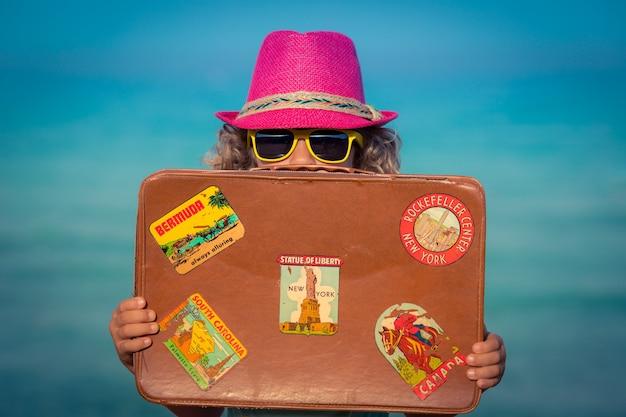 해변에서 빈티지 가방으로 행복 한 아이
