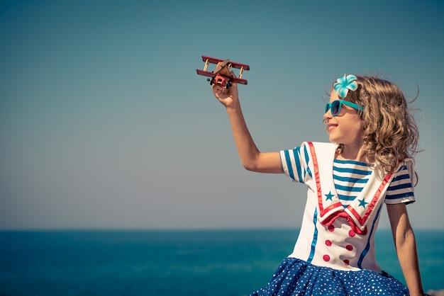 빈티지 장난감 비행기와 함께 행복 한 아이 아이 여름 휴가 여행 및 모험 개념에 재미