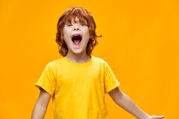 大きく開いた口の楽しい黄色の背景tシャツエネルギーモデルと幸せな子