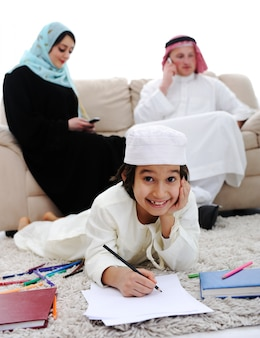 家族と家で宿題をする幸せな子供